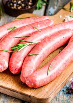 raw homemade sausages on cutting board with rosemary on rustic table